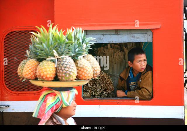 Uma mulher vendendo frutas, um rapaz a olhar para fora da janela de um comboio, Hispaw, Estado de Shan, Mianmar, Imagens de Stock