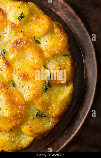 Galettes de batata ou Anna enfeitada com tomilho fresco, o sal e a pimenta e servido em uma placa rústico. Imagens de Stock