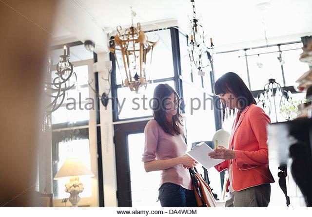 Fêmea de proprietário de negócios ajudando o cliente a loja de mobiliário Imagens de Stock
