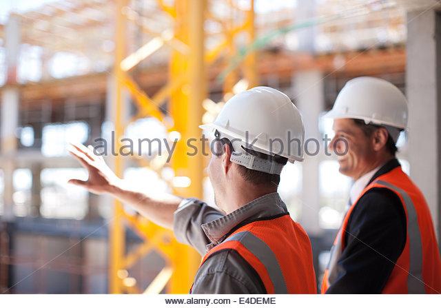Os trabalhadores da construção civil a trabalhar no local de construção Imagens de Stock
