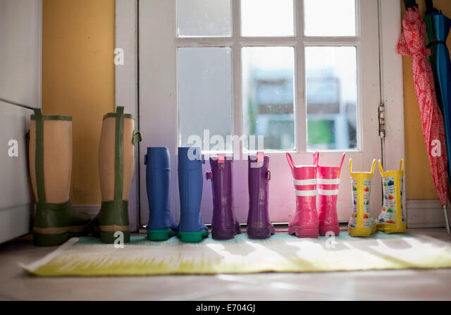 Arrumado linha de botas de borracha na porta traseira Imagens de Stock