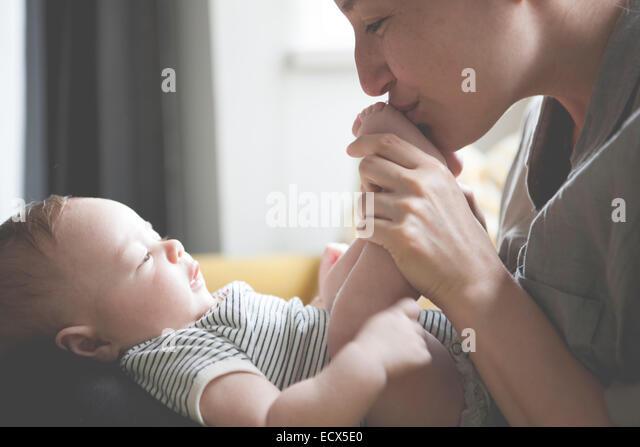 Mãe exploração e a beijar os pés do bebé Imagens de Stock