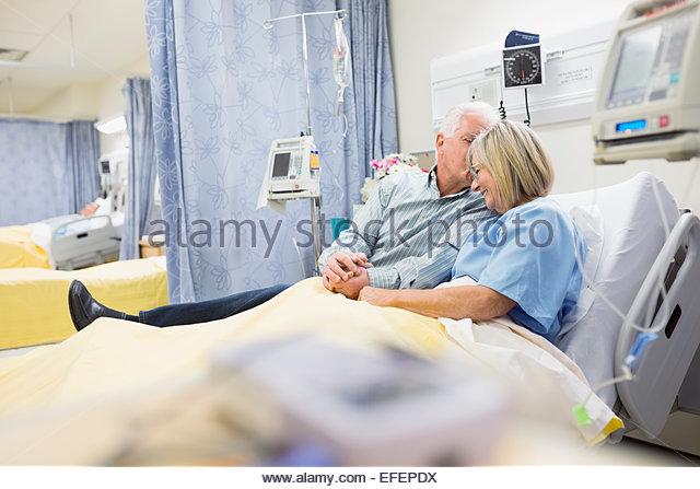 Marido reconfortante esposa em cama de hospital Imagens de Stock
