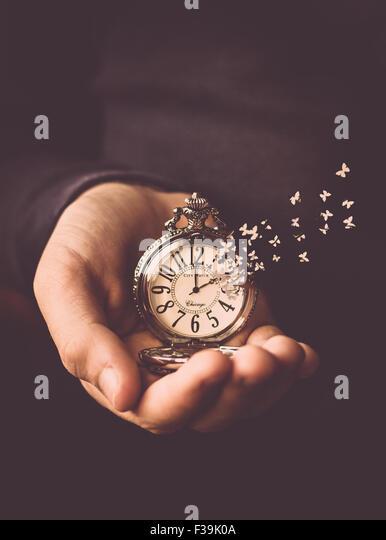 Homem segurando um relógio em sua mão com o tempo a voar o relógio rosto como borboletas Imagens de Stock