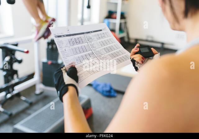 Mulher tendo o tempo enquanto atleta fazendo pull-ups no ginásio Imagens de Stock