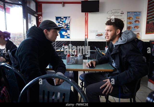 Dois estudantes do sexo masculino de comer uma refeição ligeira no Café Imagens de Stock