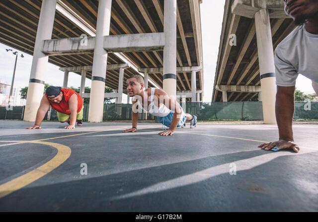 Ângulo Baixo vista de amigos no basquetebol fazendo push ups Imagens de Stock