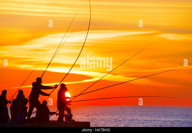 Grupo de pescador no cais ao pôr-do-sol. Porto, Portugal Imagens de Stock