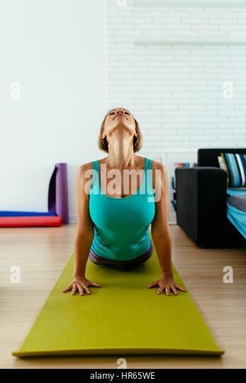 Mulher atleta praticando ioga sobre um tapete verde piscina. fotografia vertical Imagens de Stock