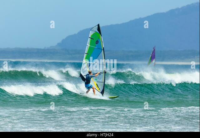 Windsurfista surf em mares pesados com ondas grandes em Seven Mile Beach, Gerroa, Costa Illawarra, Nova Gales do Imagens de Stock