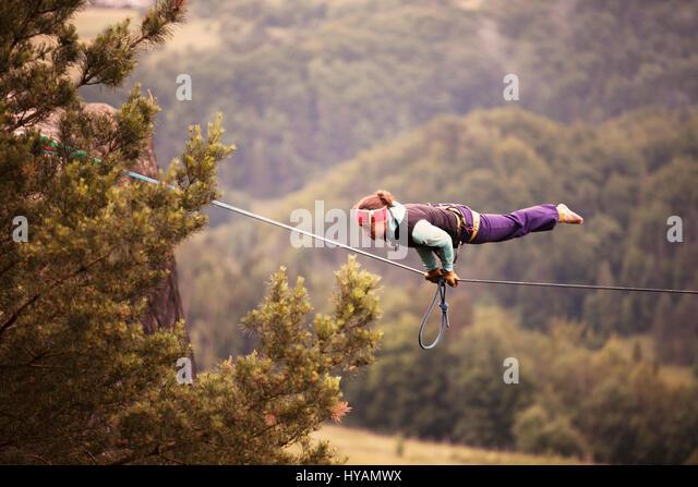 OSTROV, REPÚBLICA CHECA: uma fêmea slackliner mostra off no alto-fio. Da confecção de roupa Imagens de Stock