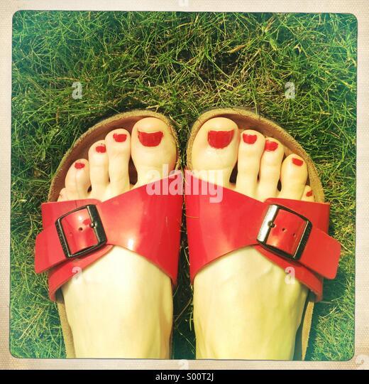 Dedos pintados nas sandálias sobre a grama Imagens de Stock