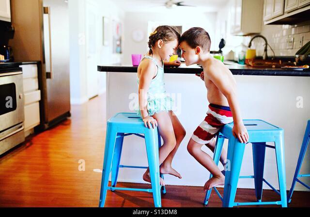 Duas crianças em fatos de banho sendo tola em a hora da refeição em casa na cozinha moderna Imagens de Stock