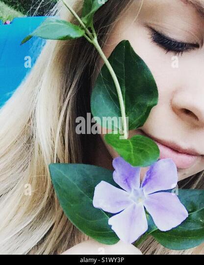 Menina com uma flor roxa Imagens de Stock