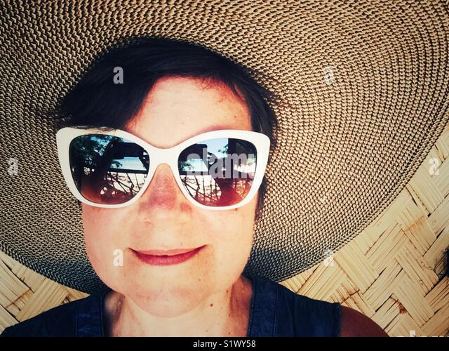 Mulher, sorrindo feliz em big sunhat e 50-s branco estilo óculos de sol directo Imagens de Stock